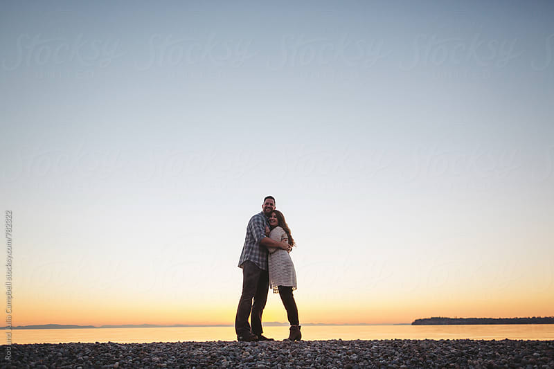 Happy couple enjoying life together at sunset - looking at camera by Rob and Julia Campbell for Stocksy United