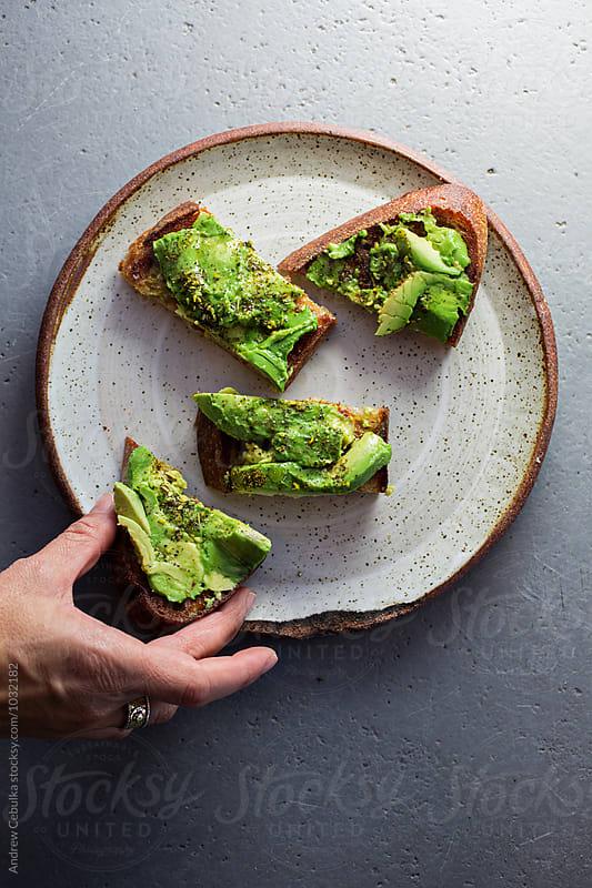 Avocado toast on white ceramic plate by Andrew Cebulka for Stocksy United