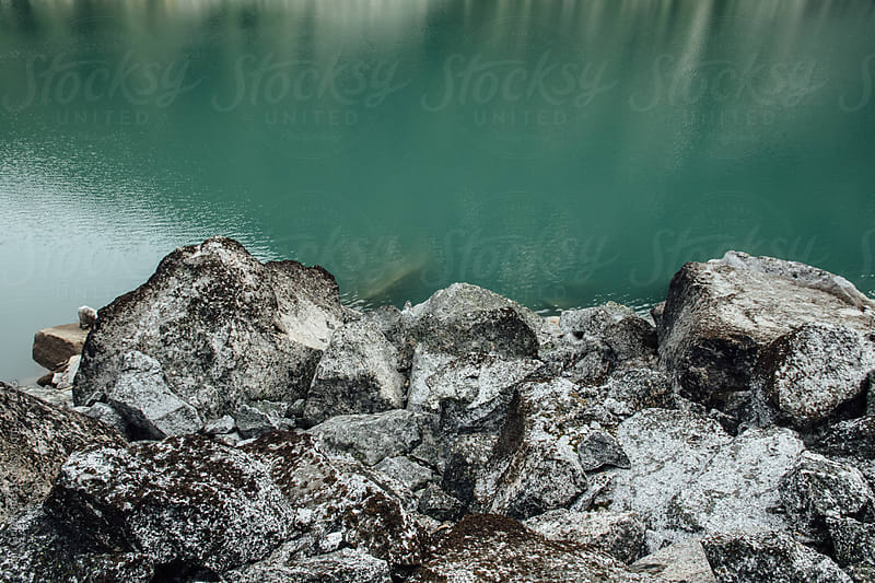 Grey boulders against teal water by Tari Gunstone for Stocksy United