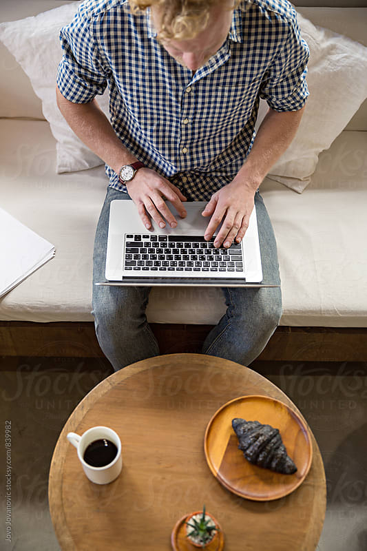 Young man working on a laptop by Jovo Jovanovic for Stocksy United