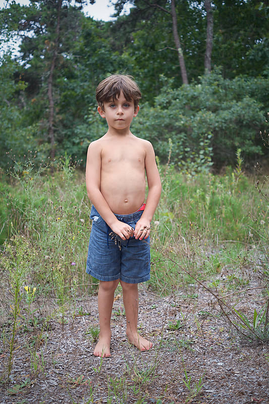 Boy standing in tall grass shirtless by Lucas Saugen for Stocksy United