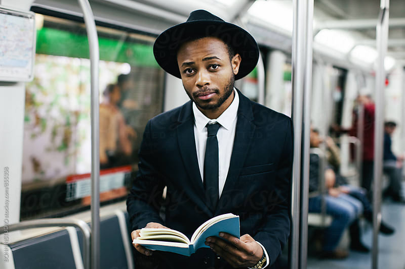 Stylish businessman reading a book on subway. by BONNINSTUDIO for Stocksy United