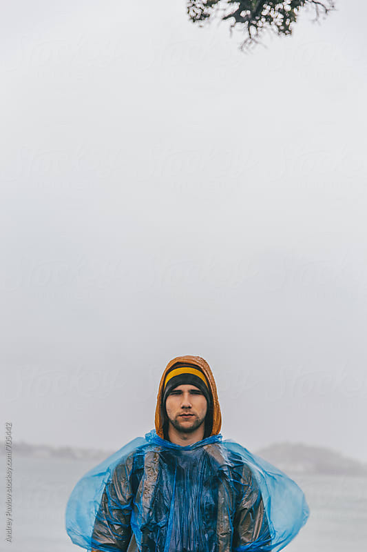 Man covered by raincoat looking at camera by Andrey Pavlov for Stocksy United