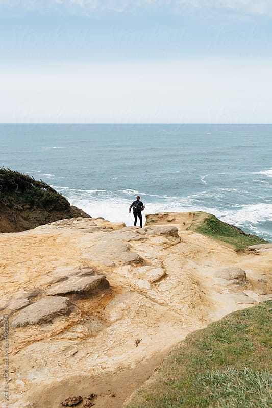 Man standing on the edge of a lookout point over the ocean by KATIE + JOE for Stocksy United