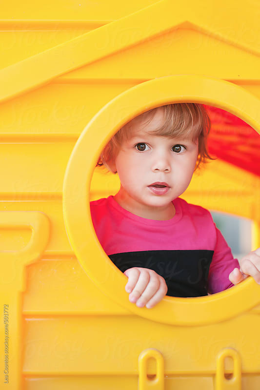 Little girl looking out of the window of a yellow playhouse with a curious face. by Lea Csontos for Stocksy United