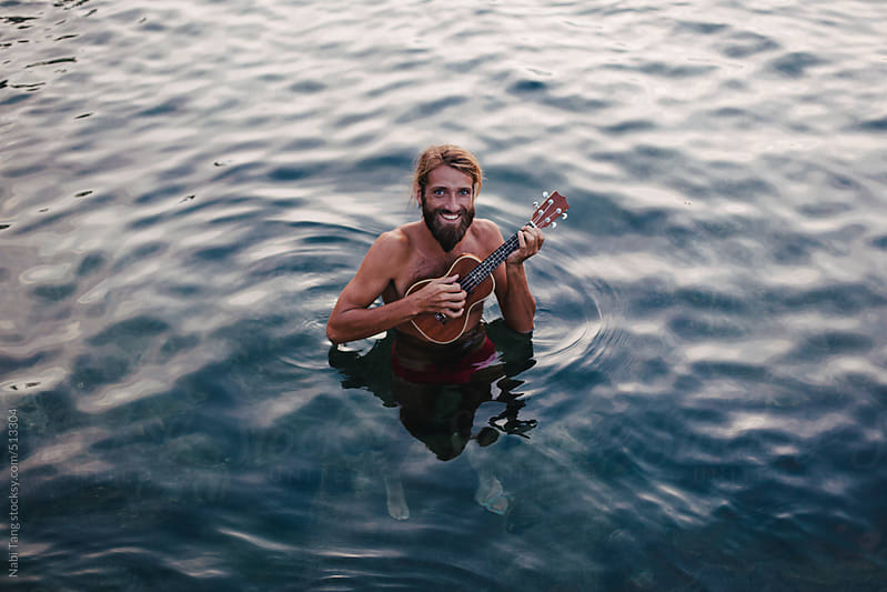 A handsome hippie playing ukulele in the sea by Nabi Tang for Stocksy United
