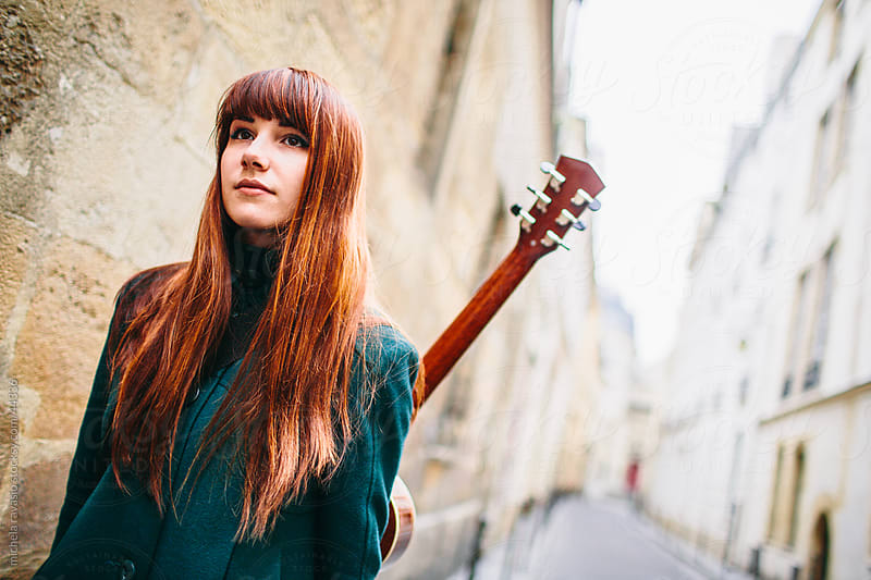 Cute young woman walking on the street with her guitar by michela ravasio for Stocksy United