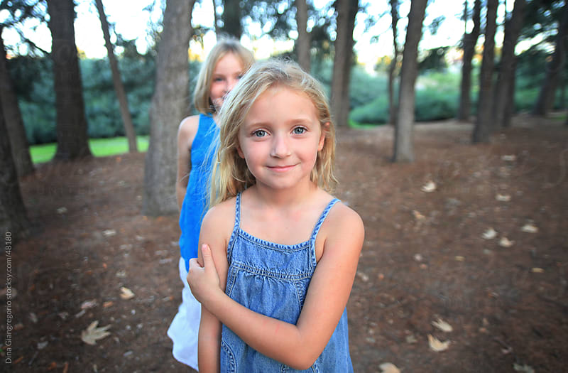 Two blonde girls, one in foreground smiling softly wearing blue dress in wilderness park with trees by Dina Giangregorio for Stocksy United