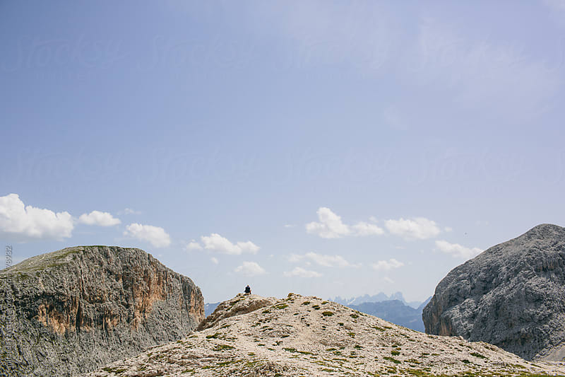 Man sitting on a rock on top of the mountain by michela ravasio for Stocksy United