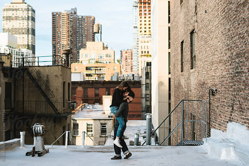 Young couple having fun on a rooftop in the city by Simone Becchetti for Stocksy United