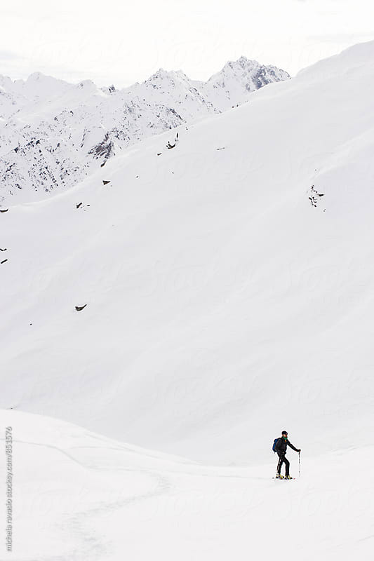 Man hiking in the snowy mountain by michela ravasio for Stocksy United