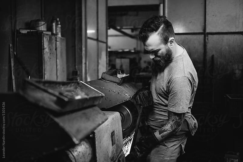 tattoed metal worker grinding metal plate in a workshop - black and white by Leander Nardin for Stocksy United