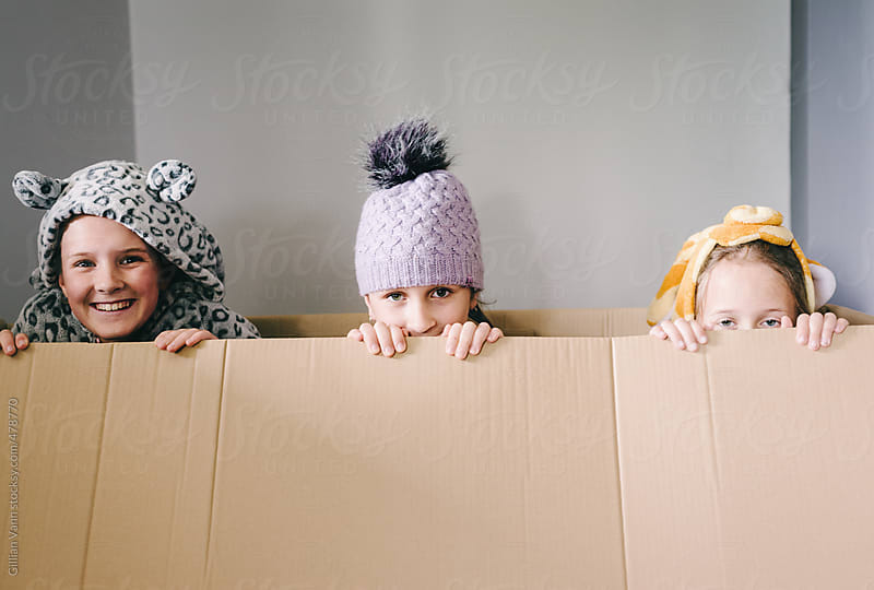 three children playing in an empty cardboard box by Gillian Vann for Stocksy United