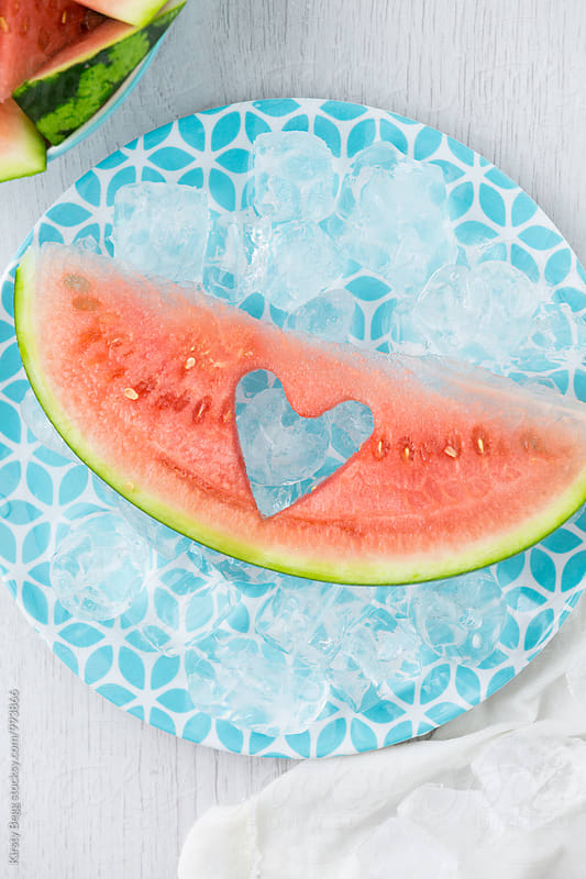 A slice of watermelon  on ice with a heart shape cut out by Kirsty Begg for Stocksy United