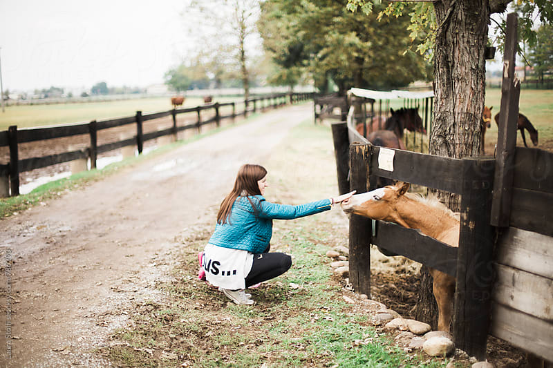 Beautiful woman bending down to caress colt standing behind wooden fence by Laura Stolfi for Stocksy United
