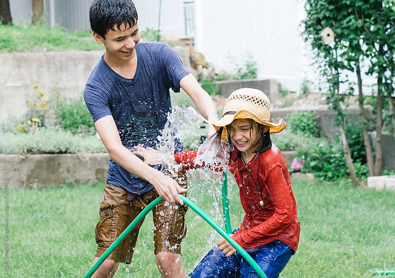 Brothers having water fight with hose by kelli kim for Stocksy United