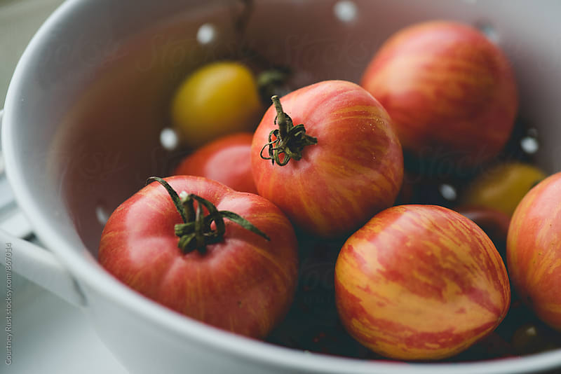heirloom tomatoes in a bowl by Courtney Rust for Stocksy United