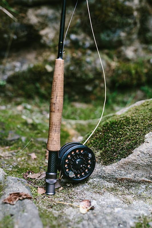 Fishing rod and reel on rocky riverbank ready to catch fish by Matthew Spaulding for Stocksy United
