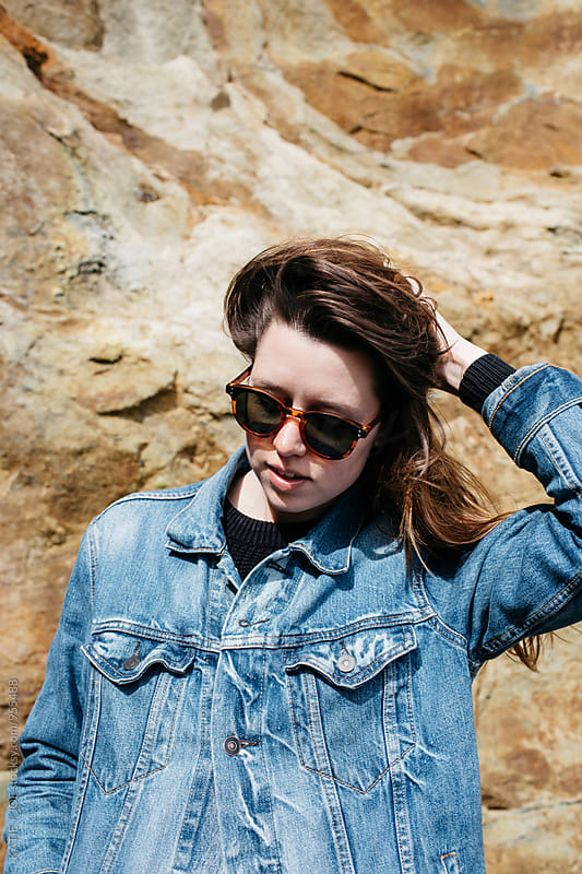 Woman wearing sunglasses and a denim jacket standing by a red rocky wall by KATIE + JOE for Stocksy United
