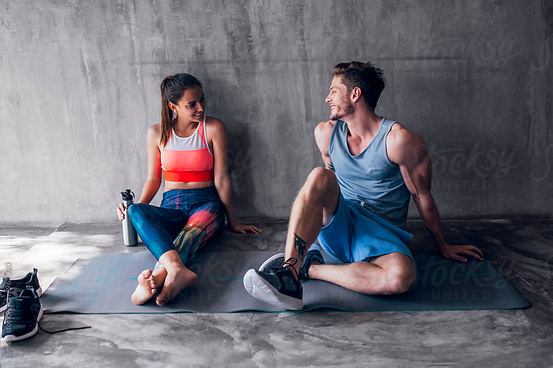Man and Woman in Sportswear Sitting on the Floor and Chatting by Lumina for Stocksy United