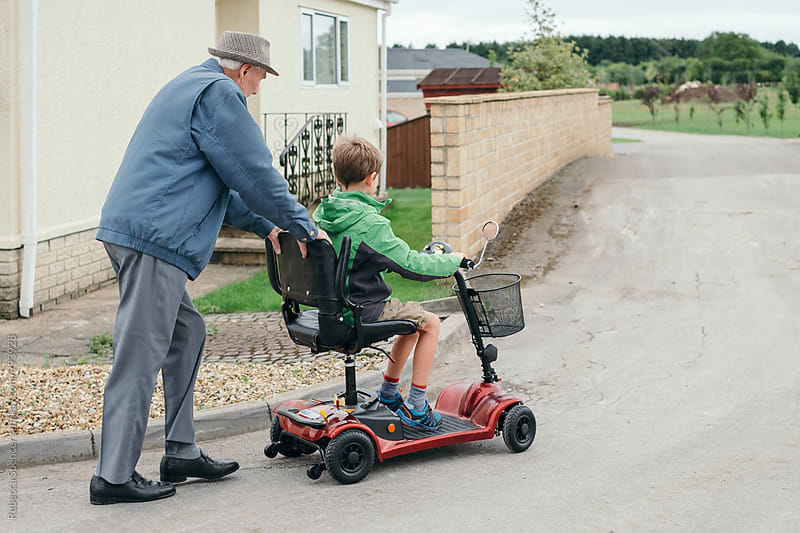 Young boy learning to drive scooter with Grandad's help by Rebecca Spencer for Stocksy United