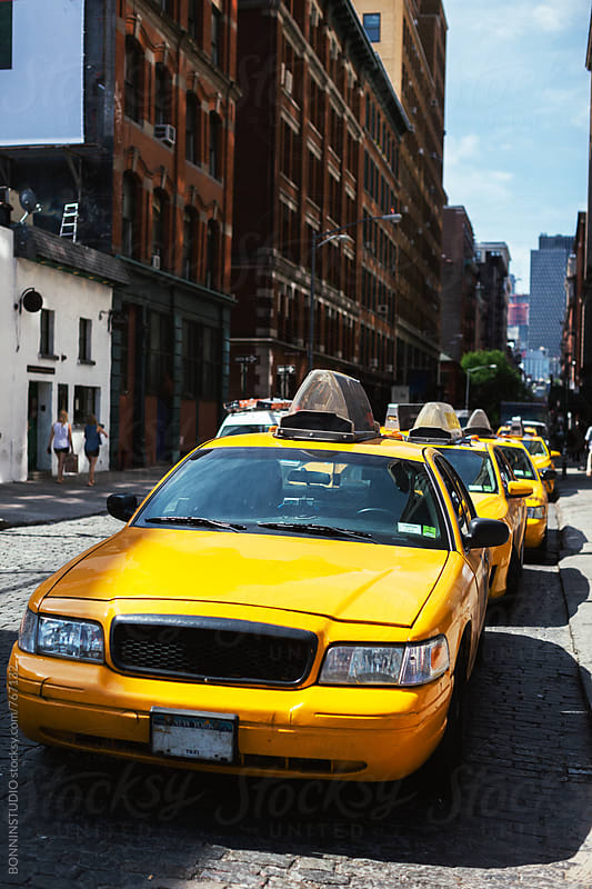 Taxis parked on the street in a sunny day.  by BONNINSTUDIO for Stocksy United