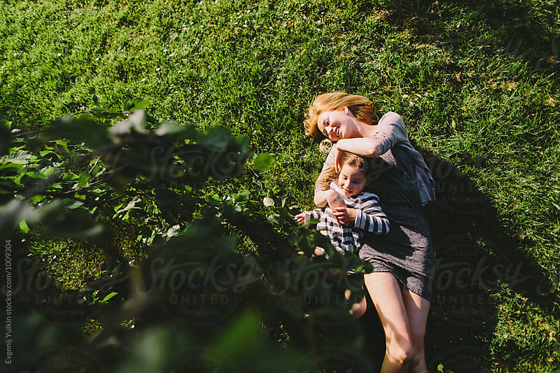 Mother embracing her daughter laying under the tree on the grass by Evgenij Yulkin for Stocksy United