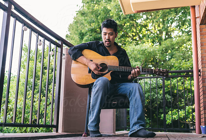 Songwriter playing acoustic guitar by Juri Pozzi for Stocksy United