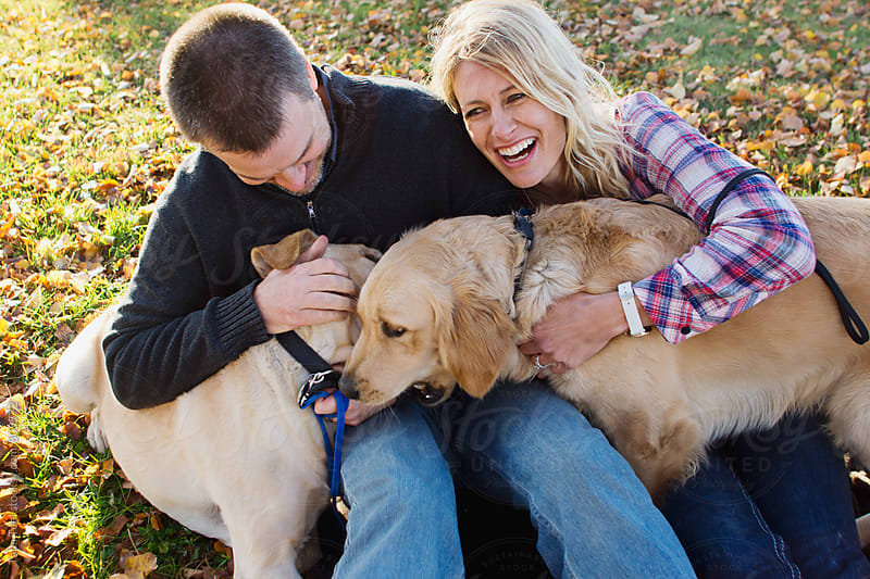 Couple happily plays with pet dogs by Tana Teel for Stocksy United