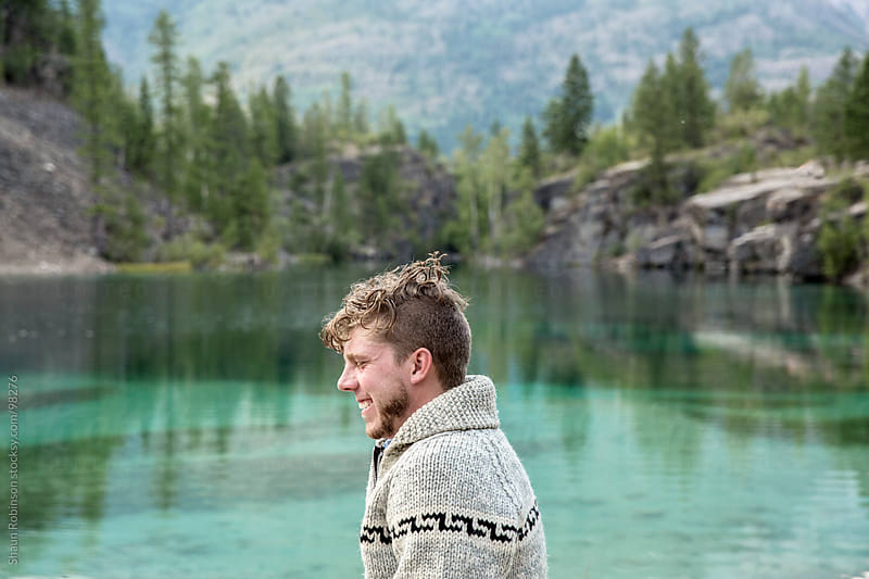 A young man sitting beside a lake by Shaun Robinson for Stocksy United