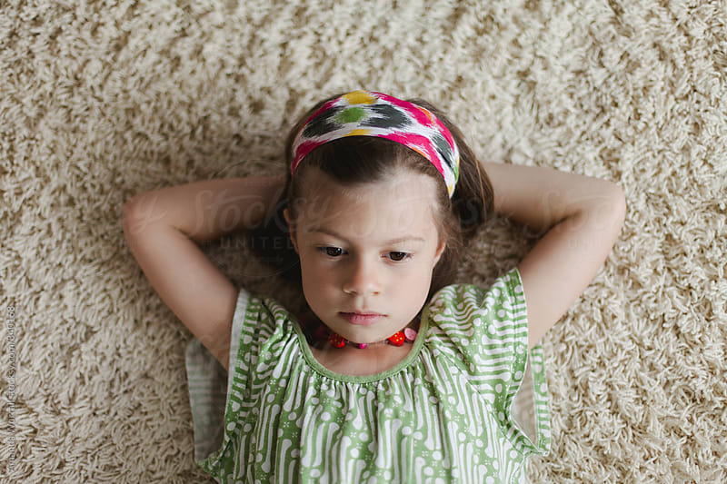 Young girl laying on carpeted floor, in serious thought by Amanda Worrall for Stocksy United