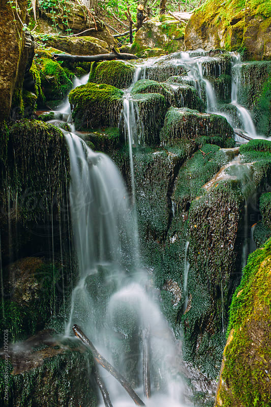 Flowing Waterfall Over Mossy Boulders In Green Forest by Zocky for Stocksy United