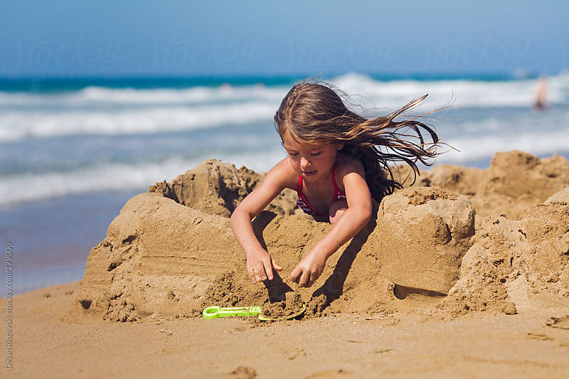 Little girl making sandcastle  by Dejan Ristovski for Stocksy United