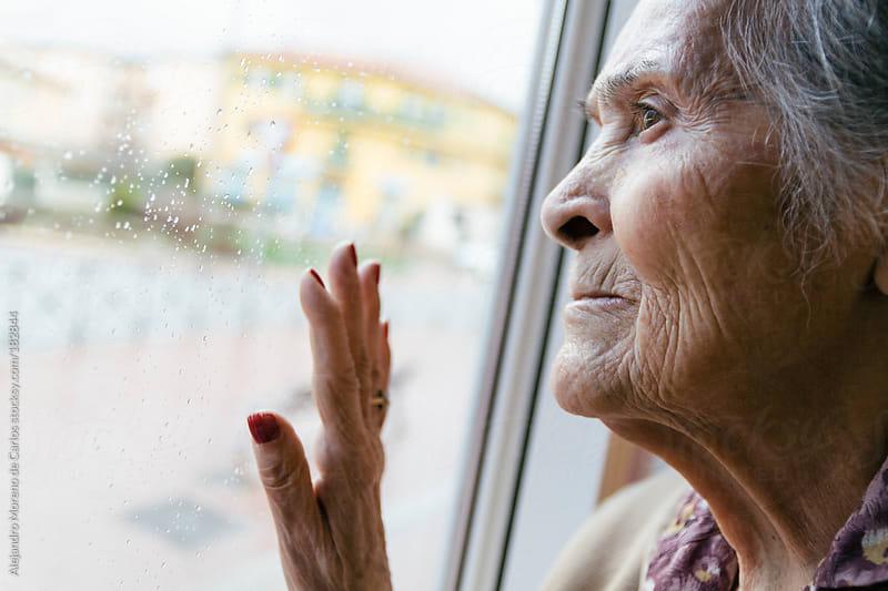 Senior woman looking through window toughtful by Alejandro Moreno de Carlos for Stocksy United