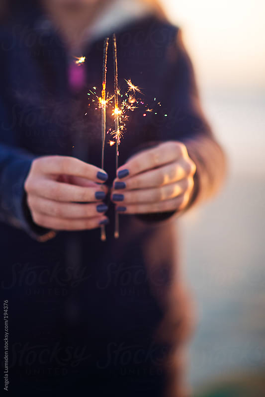 Girl with painted fingernails holding sparklers by Angela Lumsden for Stocksy United