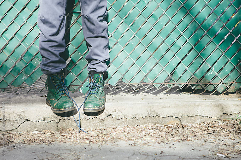 Stylish Young Man's Green Boots with Untied Lace against Urban Fence by Joselito Briones for Stocksy United