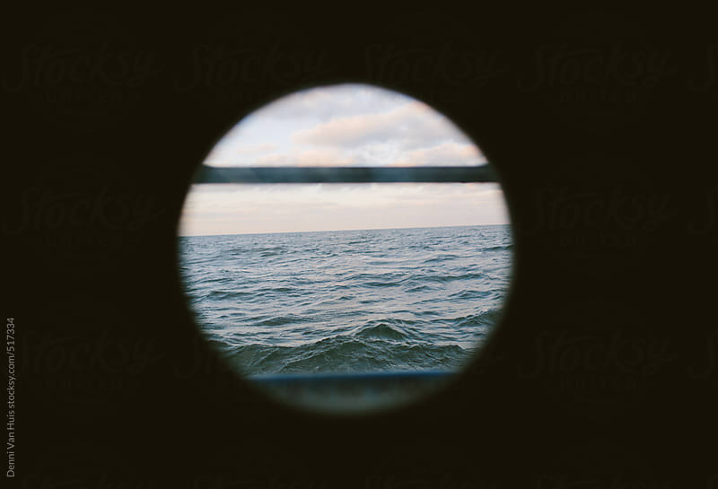 View through a porthole of a sailboat onto a calm ocean. by Denni Van Huis for Stocksy United