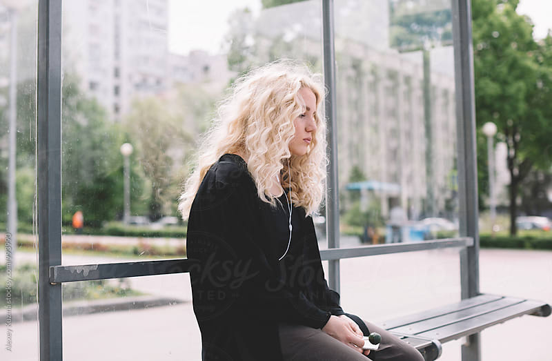 blond young woman waiting for the bus by Alexey Kuzma for Stocksy United