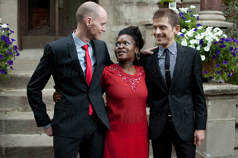 newlywed grooms converse with their wedding officiant by Margaret Vincent for Stocksy United