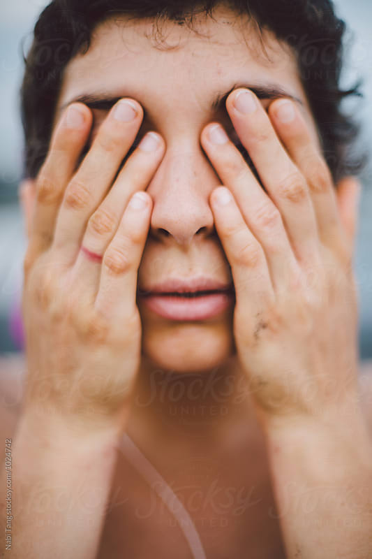Close up portrait of woman covering her eyes by Nabi Tang for Stocksy United