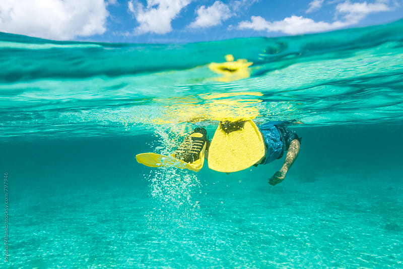 Half water half sky photo of a young man snorkeling in tropical turquoise water on one of Thailand islands by Jovana Milanko for Stocksy United