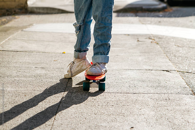 young woman legs in ripped jeans while riding skateboard on sidewalk  by Jesse Morrow for Stocksy United