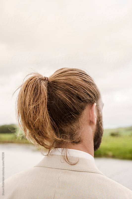 A man with pony tail looking at a pond by Shaun Robinson for Stocksy United