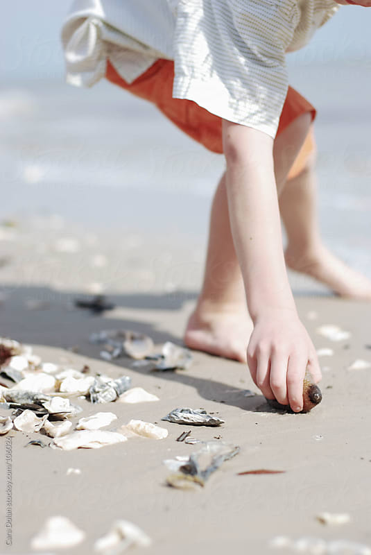 Child reaches down to pick up a sea cucumber that has washed up on a beach by Cara Dolan for Stocksy United