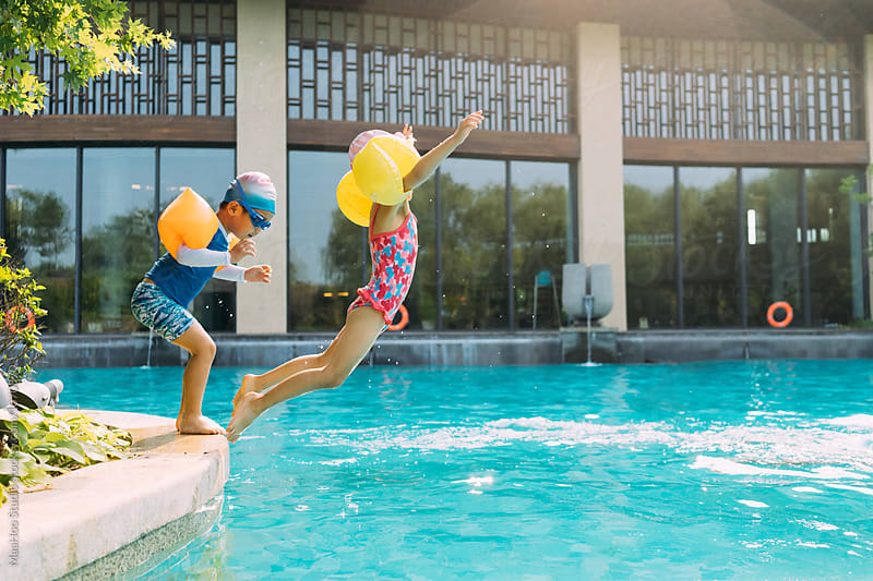 Two kids jumping into swimming pool by MaaHoo Studio for Stocksy United