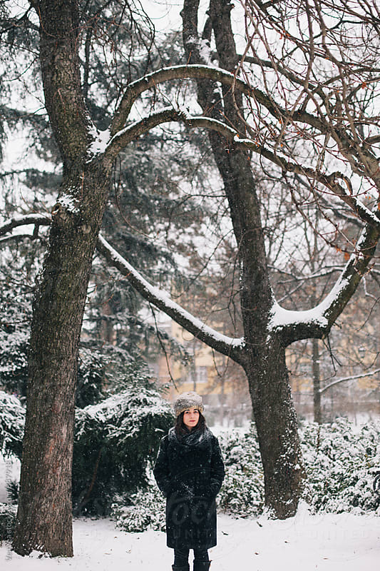 Brunette woman standing in a park during a snowy day  by VeaVea for Stocksy United