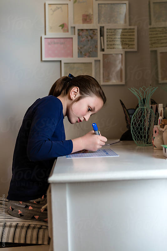 teenager doing homework in her bedroom by Gillian Vann for Stocksy United