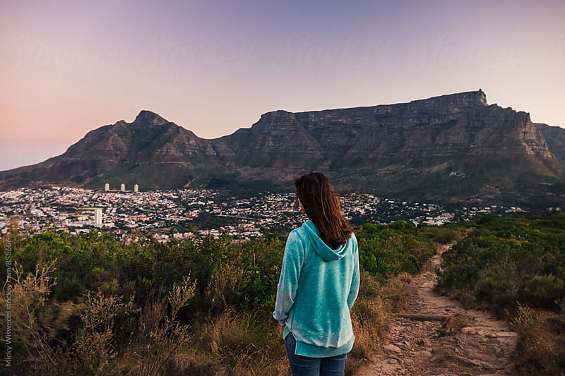 Woman on a walk stopping to enjoy the view of Cape Town city and Table Mountain by Micky Wiswedel for Stocksy United