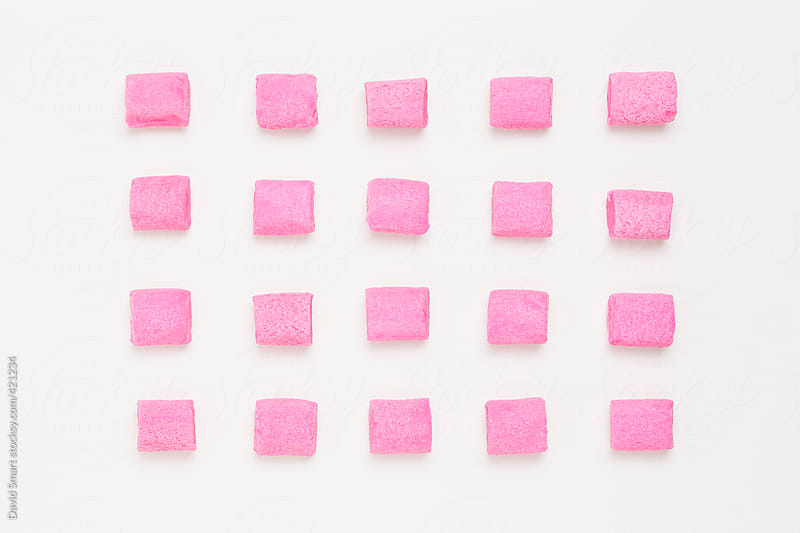 Rows of pink bubble gum on white background by David Smart for Stocksy United