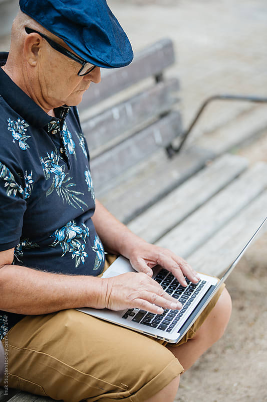 Senior man using laptop while sitting on bench by Inuk Studio for Stocksy United
